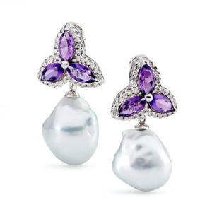 A large pair of 17 mm South Sea Cultured Pearls, baroque in shape and silver in colour, the pearls are grade 1 with a AAA luster, set on a star style setting with amethyst surrounded by 72 diamonds totaling 1.44 carats. The setting is 18 carat white gold and is a stud fitting.