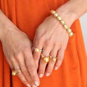 woman modelling gold pearl rings