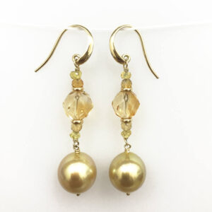 A pair of 11 mm Golden South Sea Pearls, drop shaped, grade 1 with a AAA luster and a strong gold colour set with 8.50 carats of faceted cut Citrine and 1 carat of yellow sapphire beads, with 18 carat yellow gold shepherd hooks.