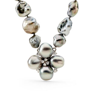A strand of Tahitian Keshi Pearls containing 36 Keshis, mid grey in colour, with a AAA luster, grade 1 and 10 to 12mm in size. At the center of the strand is a floral setting, with 4 silver Tahitian Keshi pearls, with 8 diamonds totaling 0.35 carats. The necklace is strung to 49 cm in length and fastens with a baroque shaped 18 carat white gold clasp